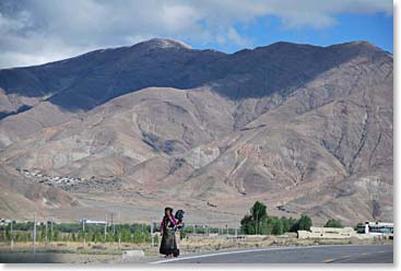 A woman walks along a remote section of the Friendship Highway