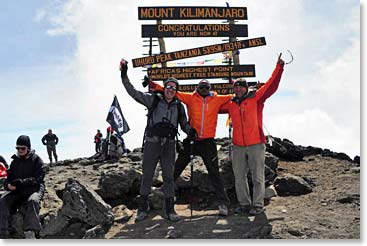 Climbers celebrate in front of the new summit sign on Kili