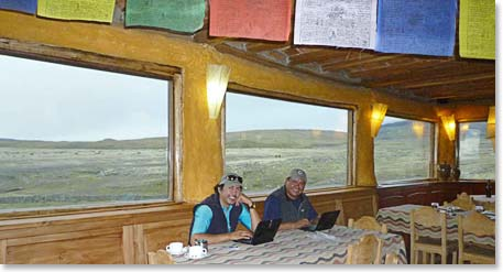 Berg Adventures guides Joaquin and Osvaldo working on dispatches in a comfortable mountain hut.