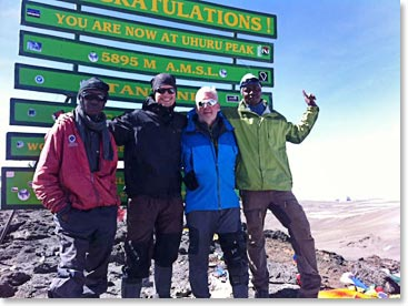 Tim and Rafael stand on the summit with guides Julius and Emmanuel