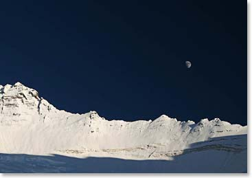 The moon rises dramatically over the snowy peaks of the Himalaya
