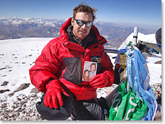 Todd on the summit of Aconcagua holding a picture of girlfriend, Heather