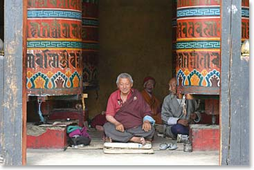 A happy monk rests between giant prayer wheels