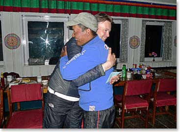 A climber and Sherpa guide share a warm hug after a successful summit.